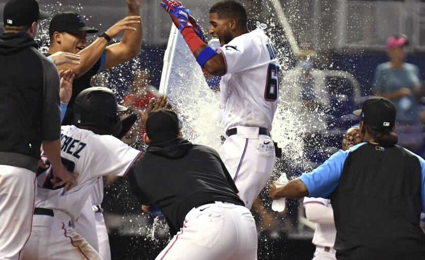 Miami Marlins' Lewin Diaz, center, celebrates with teammates after hitting a two-run walkoff home run against the Pittsburgh Pirates in the 10th inning of a baseball game, Sunday, Sept. 19, 2021, in Miami. (AP Photo/Jim Rassol)