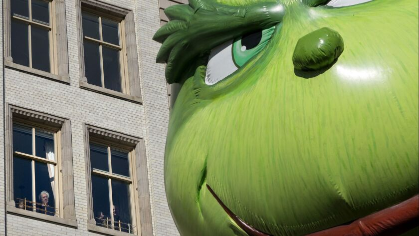 The Grinch balloon passes by windows of a building on Central Park West during Macy's Thanksgiving D