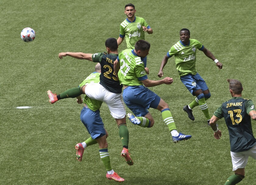 Portland Timbers defender Bill Tuiloma, left, and Seattle Sounders defender Shane O'Neill, right, go after the ball during first half of an MLS soccer match in Portland, Ore., Sunday, May 9, 2021. (AP Photo/Steve Dykes)