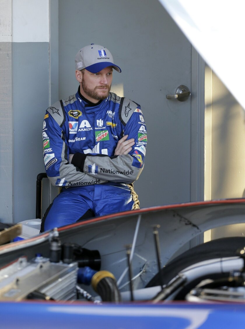 Dale Earnhardt Jr. watches as the crew works on his car during practice for the NASCAR Daytona 500 auto race at Daytona International Speedway, Wednesday, Feb. 17, 2016, in Daytona Beach, Fla. (AP Photo/Terry Renna)