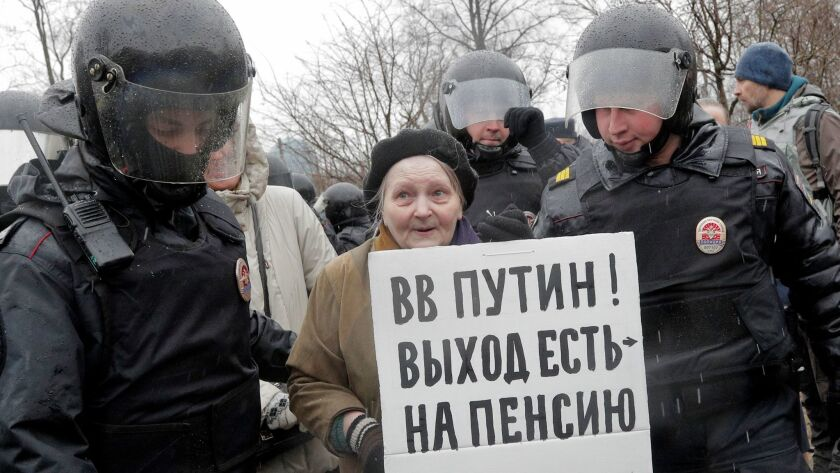 "Police detain a woman holding a poster that reads, ""Putin, you can retire,"" at a rally in St. Petersburg, Russia, on April 29, 2017."