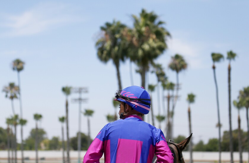 A jockey cools down his horse after a race at Los Alamitos in June 2019.