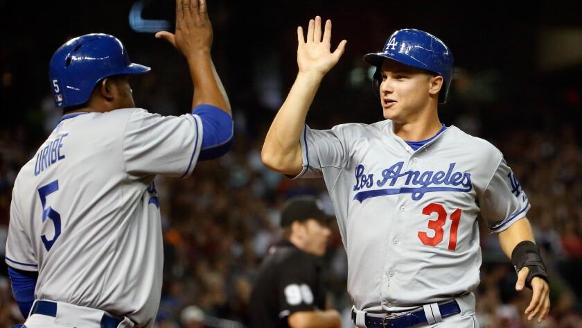 Dodgers center fielder Joc Pederson, right, celebrates with third baseman Juan Uribe after both players scored runs during a loss to the Arizona Diamondbacks on April 10.