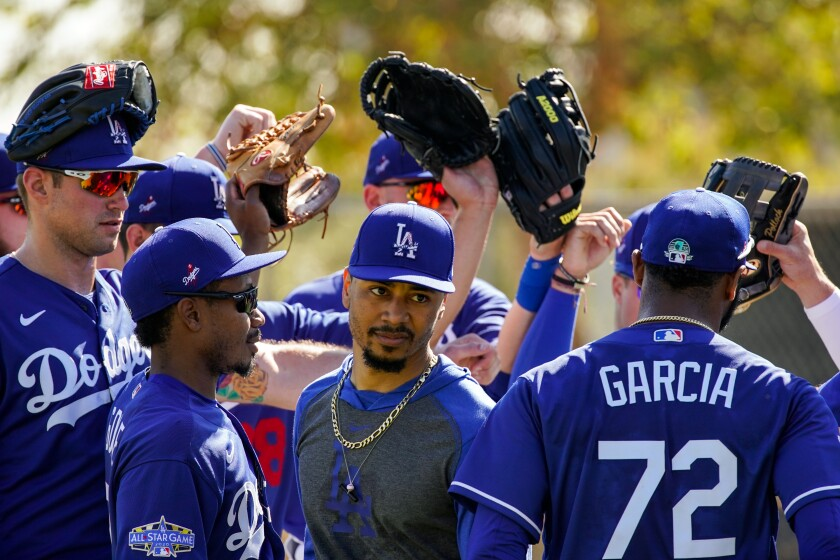 Dodgers right fielder Mookie Betts is surrounded by teammates during spring training at Camelback Ranch on Feb. 19.