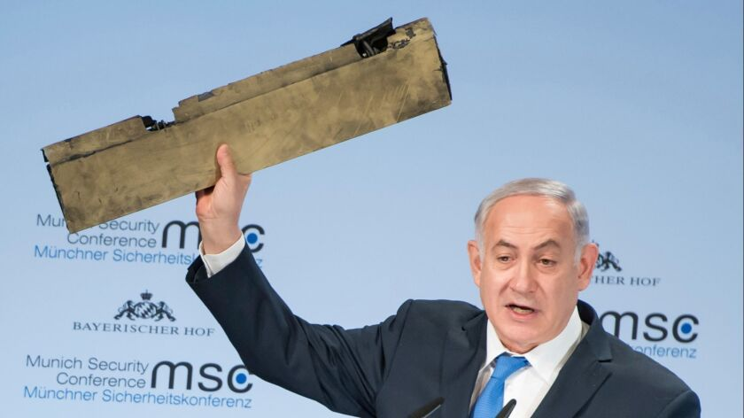 Israeli Prime Minister Benjamin Netanyahu holds what he said was part of a downed Iranian drone during his speech at the Munich Security Conference in Germany on Feb. 18, 2018.