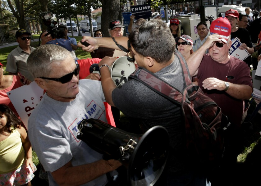 An anti-Donald Trump protestor, center, pepper sprays a crowd of Trump supporters outside Anaheim City Hall.