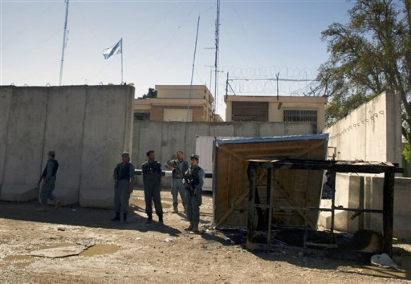 Afghan policemen stand guard near a burnt booth, right, at the compound of UN's office, which was attacked by protesters on Friday during a demonstration to condemn the burning of a copy of the Muslim holy book by a U.S. Florida pastor, in Mazar-i- Sharif north of Kabul, Afghanistan on Saturday, April. 2, 2011. Afghans angry over the burning of a Quran at a small Florida church stormed a U.N. compound in northern Afghanistan on Friday, killing seven foreigners, including four Nepalese guards. (AP Photo/Mustafa Najafizada)