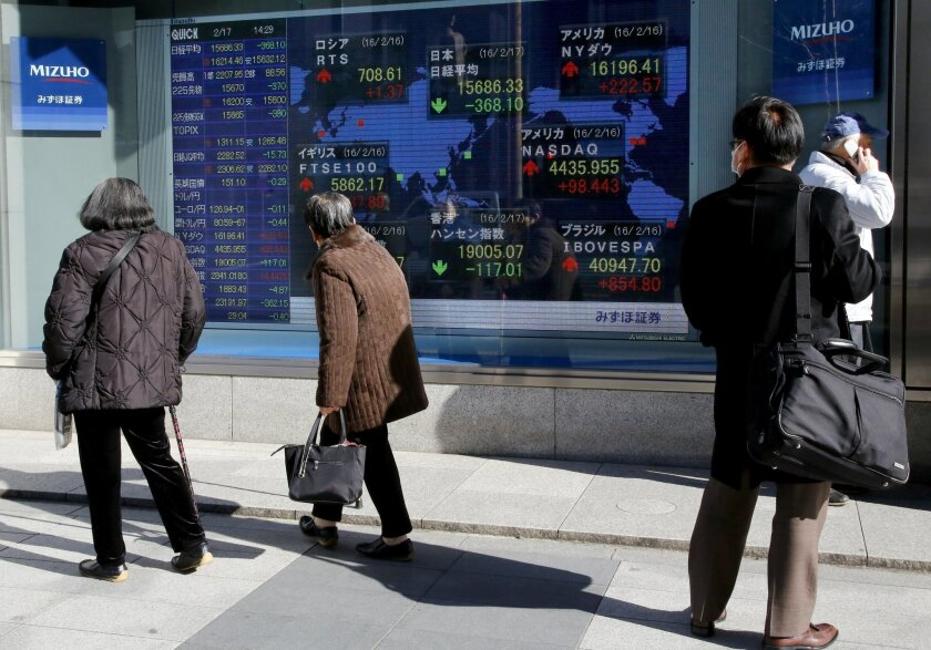 People look at the electronic board of a securities firm in Tokyo, Wednesday, Feb. 17, 2016. Asian stock markets were mostly higher Wednesday as investors weighed the potential outcome of a preliminary agreement between Russia and Saudi Arabia to hold off on further increases in crude oil productio