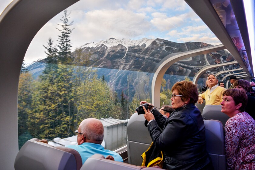 Passengers aboard the Rocky Mountaineer train enjoy one of the dome cars, giving them spectacular views of the Canadian Rockies as they climb toward Banff in Alberta, Canada.