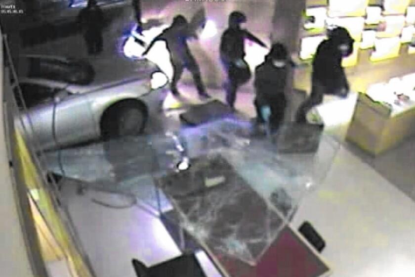 Surveillance video shows masked burglars crashing a car into a Louis Vuitton store in the Chicago suburbs.