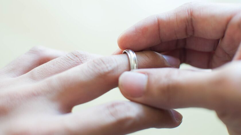 A man is holding his wedding ring conceptual