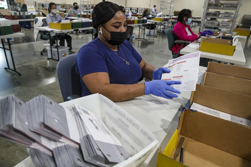 Election worker Tameka Augustus inspects a ballot that have been received for the Sept. 14, recall election