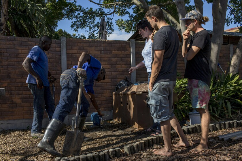 Gabby De Wet, center, whose family owns De Wet's Wellpoints and Boreholes, talks Feb. 18, 2018, with her team and client Carsten Hensel, right, after installing a wellpoint in his backyard.