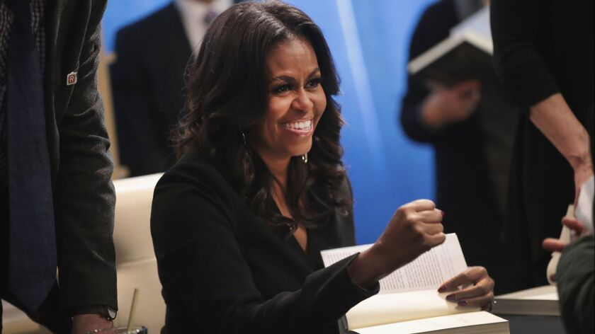 """Michelle Obama signs """"Becoming"""" on Tuesday."""