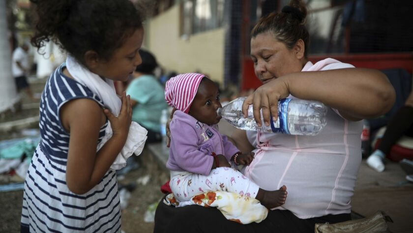A Central American woman gives water to a baby as a large group of immigrants sets up camp for a few days at a sports center in Matias Romero in Mexico's Oaxaca state late Monday.