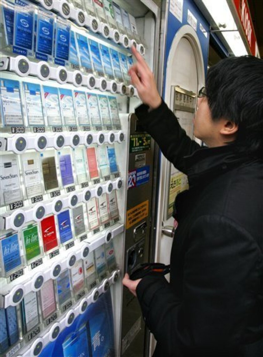 FILE - In this Dec. 15, 2006, a man buys a cigarette by a vending machine in Tokyo. On Oct. 1, 2010, Japan is imposing a 40 percent tax hike on cigarettes, effectively raising the price of a pack on the most popular brands by a third, to encourage people to quit smoking. (AP Photo/Shizuo Kambayashi, File)