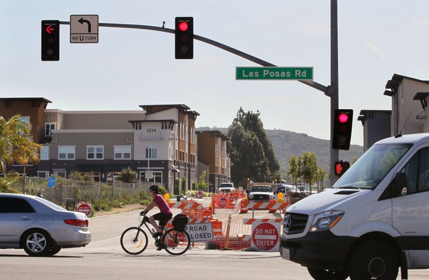 A cyclist on northbound on N. Las Posas Road passes by Armorlite Drive, where one side of the street is closed for construction to add storm treatment underground, and bike lines and sidewalks along the road. The project could be completed by August or September.