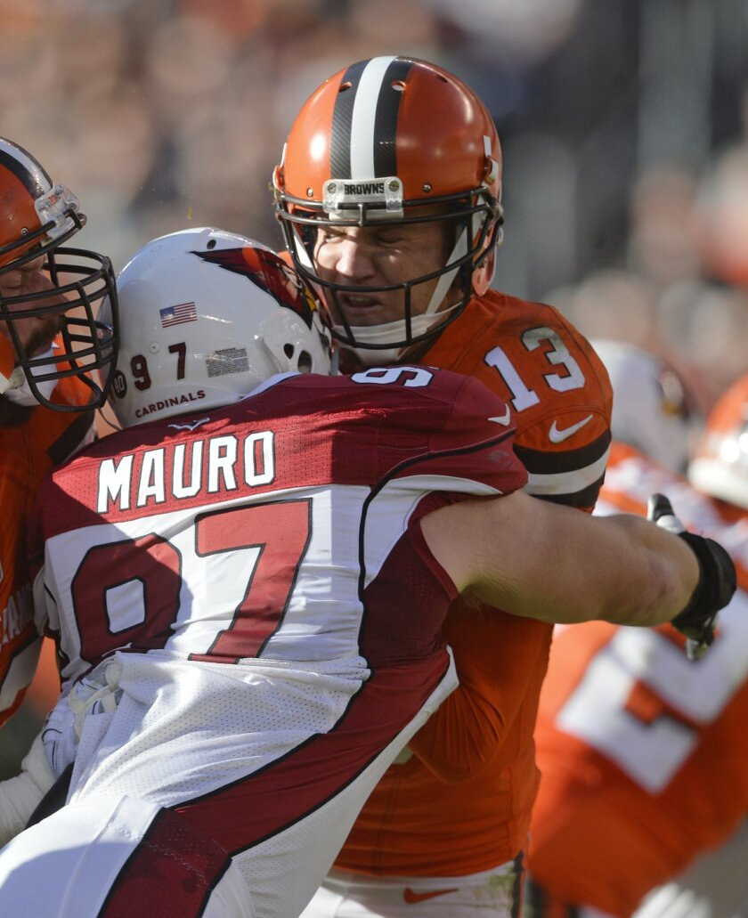 This Sunday, Nov. 1, 2015, photo shows Arizona Cardinals nose tackle Josh Mauro (97) tackling Cleveland Browns quarterback Josh McCown (13) during an NFL football game, in Cleveland. Browns coach Mike Pettine says McCown is sore and it's not yet known if he'll play Thursday in Cincinnati. McCown in