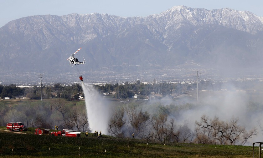 Fire crews get a handle on a brush fire, dubbed the Mann fire, that broke out in Norco on Tuesday,