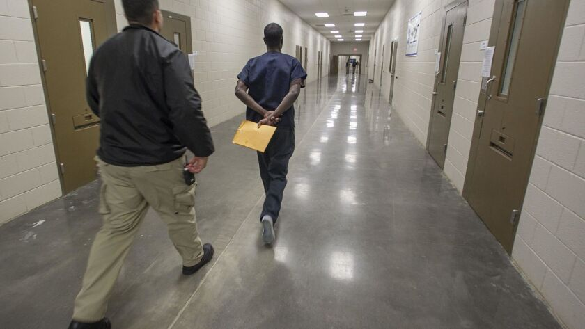 An asylum seeker is moved through the ICE Imperial Regional Detention Facility in Calexico. About 40% of detainees there are from India. Many say they've been persecuted under their country's Hindu nationalist government.