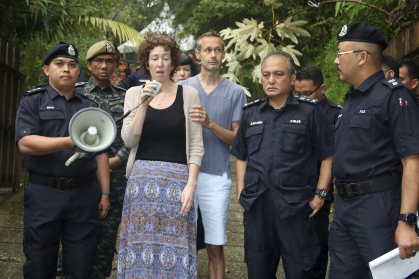 FILE - In this Aug. 10, 2019, file photo, Meabh Quoirin, center left, the mother of then missing girl Nora Anne Quoirin, speaks to police officers as father Sebastien Quoirin, center right, stands beside her in Seremban, Negeri Sembilan, Malaysia. Quoirin said Wednesday, Nov. 11, 2020, that criminal evidence may have been lost as police were slow to act on the possibility that her daughter could have been abducted. (Malaysia Information Ministry via AP)