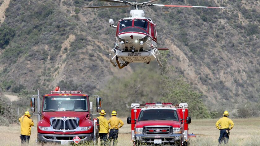 An OCFA helicopter lands after dropping search and rescue members into areas that have not been alre