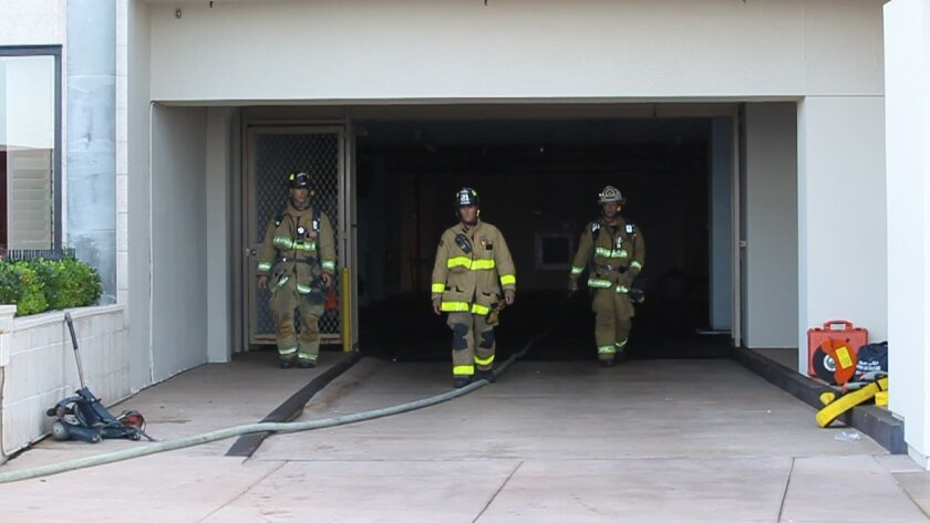 Firefighters walked from the underground parking where the explosion and ensuing fire took place.