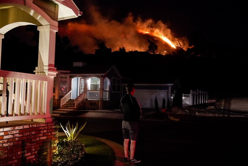Oakridge Estates resident Manuel Negrete gazes at the Saddleridge fire as his neighbors evacuate on Thursday night.