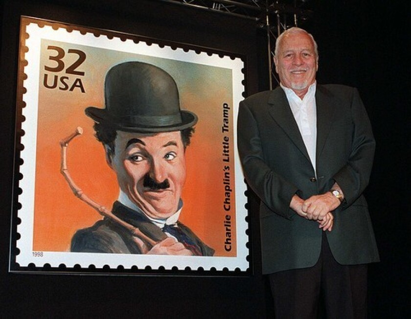 "Sydney Chaplin stands beside the postage stamp honoring his father, Charlie Chaplin, in 1998. Sydney Chaplin won a Tony Award for starring in the late 1950s musical ""Bells Are Ringing"" on Broadway."