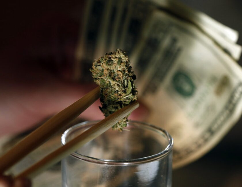 A caregiver picks out a marijuana bud for a patient at a dispensary in Denver.