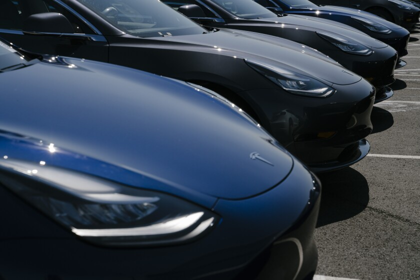 Tesla vehicles are lined up outside the carmaker's factory in Fremont, Calif.