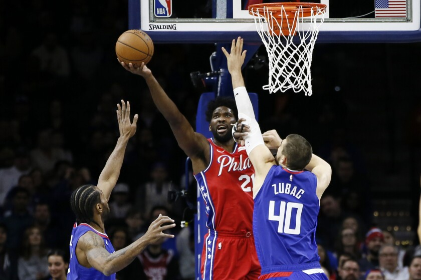 Clippers center Ivica Zubac and forward Kawhi Leonard try to prevent 76ers center Joel Embiid from scoring during a game Feb. 11, 2020, in Philadelphia.