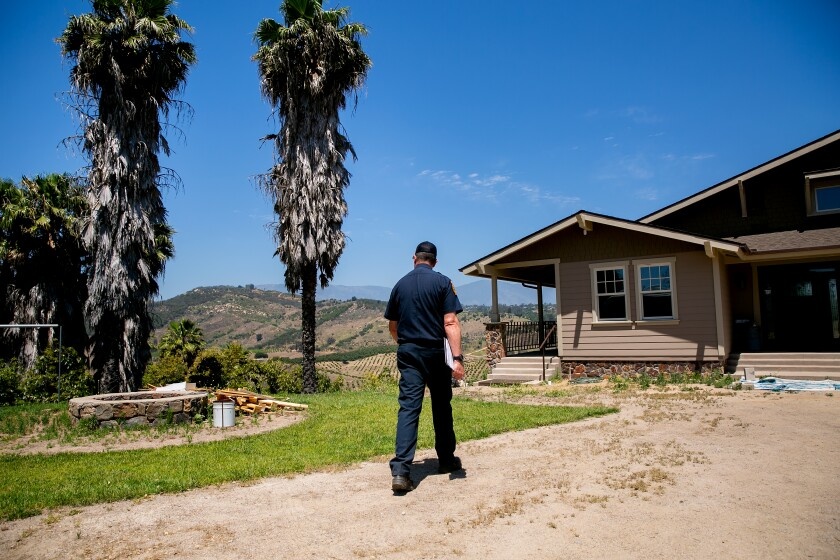 CalFire inspector David Dugger conducts defensible space inspections at a home on June 12, 2019 in Valley Center, Calif.