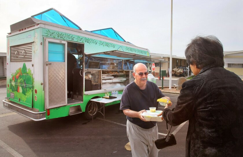 At the Vista Village Mobile Home Park volunteer Ken Vadala hands a just prepared meal to fellow volunteer Susie Early that was just cooked in the Dreams For Change food truck, at left. Susie will carry it into the adjacent mobile home park's clubhouse to serve to a senior for lunch.