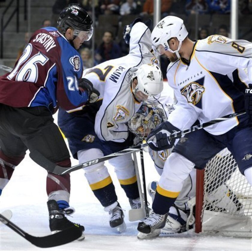 Nashville Predators defensemen Jonathon Blum (7) and Kevin Klein (8) help Predators goalie Pekka Rinne, of Finland, keep the puck from Colorado Avalanche center Paul Stastny (26) in the first period of their NHL hockey game in Denver on Thursday, March 31, 2011. (AP Photo/Joe Mahoney)