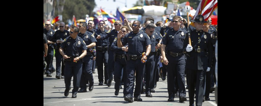 San Diego Police officers wave to the crowd as they participate in the San Diego Pride Parade.