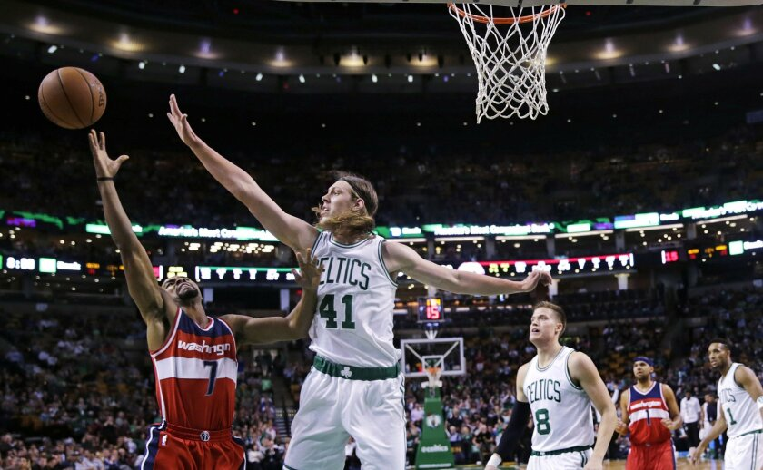 Boston Celtics center Kelly Olynyk (41) blocks a shot by Washington Wizards guard Ramon Sessions (7) during the first quarter of an NBA basketball game in Boston, Friday, Nov. 6, 2015. (AP Photo/Charles Krupa)