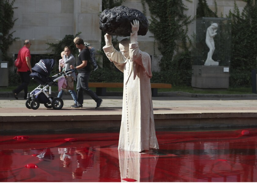 """Visitors to the National Museum walk past a new statue of the late pope, St. John Paul II, throwing a stone at a """"Poisoned Well"""" just hours before its official inauguration in the museum yard in Warsaw, Poland, Thursday, Sept. 24, 2020. The sculpture by Poland's Jerzy Kalina is said to be a response to a controversial 1999 sculpture by Italian Maurizio Cattelan in which the Polish-born pontiff was shown as being crushed by a similar stone. (AP Photo/Czarek Sokolowski)"""