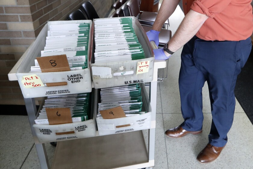 FILE - In this May 5, 2020, file photo, Jordan Smellie moves absentee ballots to be counted at City Hall in Garden City, Mich. The Michigan appeals court has denied a request to require the counting of absentee ballots received after the time polls close on Election Day. The ruling says the deadline remains intact despite voters' approval of a constitutional amendment that expanded mail-in voting. (AP Photo/Paul Sancya, File)