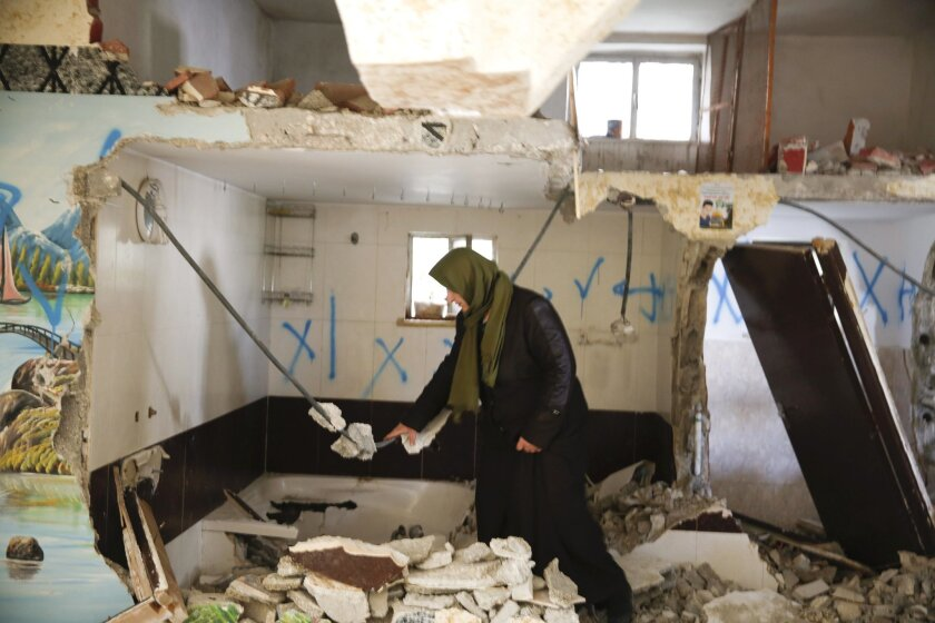Palestinian woman inspects the home of Ehab Maswada that was demolished by the Israeli army in the West Bank city of Hebron,Thursday , March 31, 2016. Maswada fatally stabbed an Israeli civilian in the West Bank city of Hebron late last year. Israel says home demolitions are an effective tool to deter attacks, but critics say the tactic amounts to collective punishment. (AP Photo/ Nasser Shiyoukhi).
