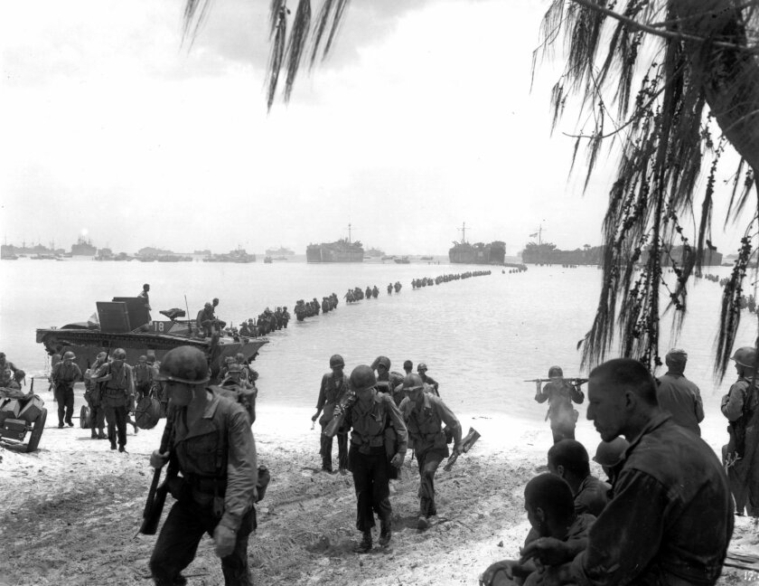 FILE - This July 1944 file photo shows U.S. Army reinforcement troops making an amphibious landing on the coral reef at Saipan beach, Mariana Islands. Racing against time, members of a Japanese organization are combing a New York military museum's World War II records for information they hope will