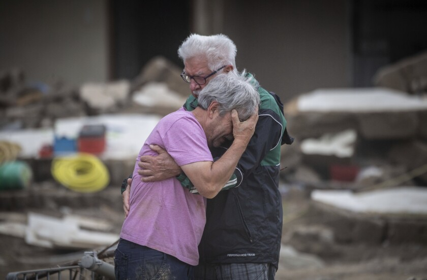 Two brothers weep in each other's arms in front of their parents' house, which was destroyed by the flood in Altenahr, Germany, Monday, July 19, 2021. Numerous houses in the town were completely destroyed or severely damaged, there are numerous fatalities. (Boris Roessler/dpa via AP)
