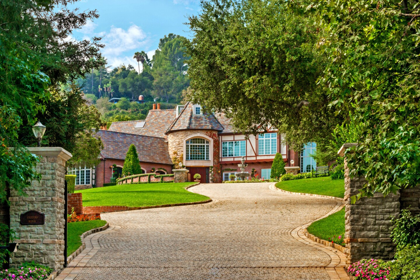 Stone pillars frame the serpentine driveway, which is made of 14,000 square feet of hand-cut Austrian cobblestone.