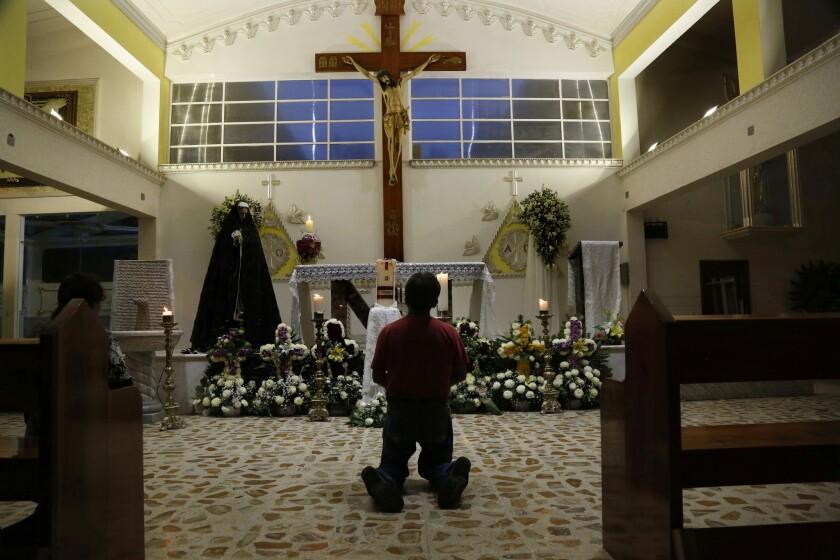 Un feligrés reza en la iglesia de Nuestra Señora de Fátima en Poza Rica, en el estado mexicano de Veracruz. Dos de los curas de la iglesia fueron hallados acribillados a balazos al costado de un camino el lunes. (AP Foto/Marco Ugarte)