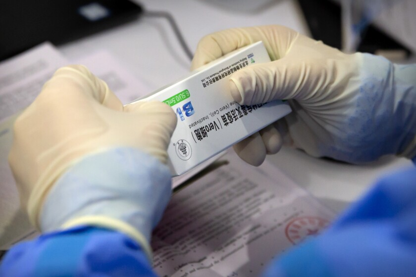 A worker opens a package of COVID-19 vaccine at a vaccination center in Beijing.