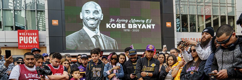 "A crowd of fans stands outside of Staples Center in front of a screen with the words ""In loving memory of Kobe Bryant 1978-2020"" and Bryant's photo."