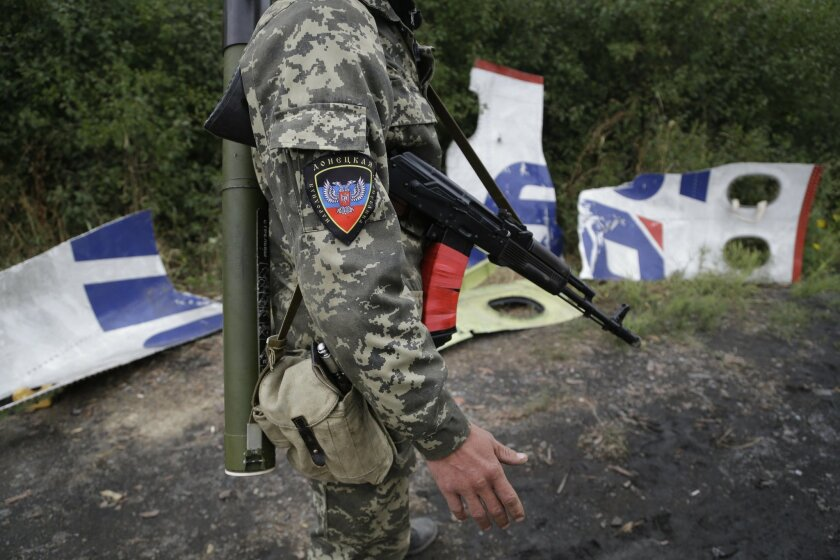 """A Pro-Russian rebel stands next to pieces of the Malaysia Airlines Flight 17 plane near village of Rozsypne, eastern Ukraine, Tuesday, Sept. 9, 2014. The Dutch team investigating the downing of Malaysia Airlines Flight 17 over Eastern Ukraine says the crash was likely caused by the plane being hit by multiple """"high-energy objects from outside the aircraft."""" The preliminary report published Tuesday by the Dutch Safety Board stopped short of saying the Boeing 777 was shot down by a surface-to-air missile, but its findings appear to point to that conclusion. (AP Photo/Sergei Grits)"""