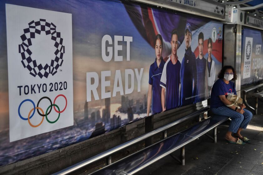A woman in a mask in Bangkok sits in front of a sign for the 2020 Olympics.
