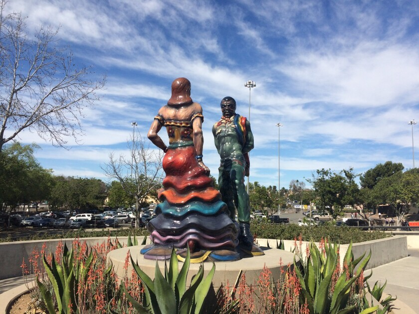 A large-scale sculpture of a pair performing Mexican folkloric dance in a public plaza