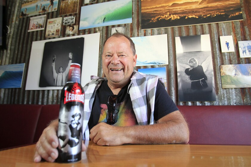 Surfing legend and Huntington Beach resident Peter Townend, 60, was honored with a Lifetime Achievement award for his career in surfing. Seen here, he proudly shows off a beer bottle with a 1980s photo of him surfing in Hawaii. Townend was the 1976 International Professional Surfers World Surfing Champion.